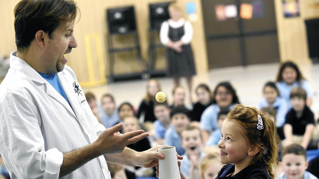 With help from Eric Krupkin, left, kindergartener Savannah Smith, right, keeps a ping pong ball aloft using a hair dryer during Krupkin's 'Eric Energy' science presentation at Carroll Lutheran School in Westminster Wednesday, March 16, 2016.
