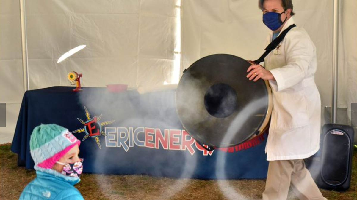 "Eric Krupkin, aka Eric Energy, shows Paitin Hankla, 4, of Owings Mills, how a carbon dioxide fog stream freezes into solid balls during ""Scientific Magic of Hanukkah,"" a program held in a tent outside Chizuk Amuno synagogue. Hankla attended the program with her grandmother, Gail Friedler of Pikesville."